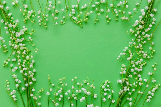 Musterrahmen des maiglöckchens, maiglöckchen auf grünem hintergrund