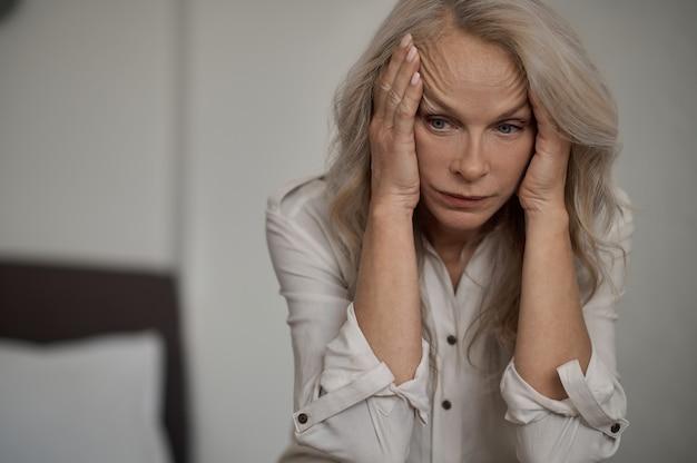 Mutlose blonde reife frau, die unter einsamkeit leidet