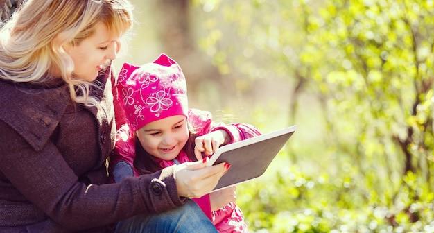 Mutter am telefon mit der tochter, die digitale tablette im park verwendet