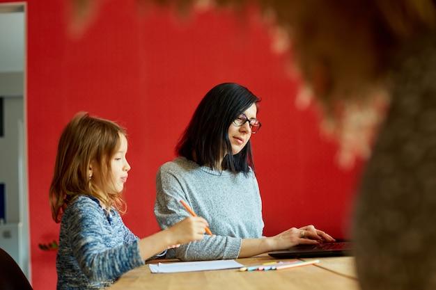 Mutter arbeitet in ihrem heimbüro an einem laptop, ihre tochter sitzt neben ihr und zeichnet, frau freiberuflich, fernarbeit und kindererziehung am arbeitsplatz.