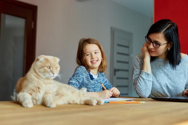 Mutter arbeitet in ihrem heimbüro an einem laptop, ihre tochter sitzt neben ihr und zeichnet, schottische katze sitzt auch auf dem tisch. freiberufliche frau, fernarbeit und kindererziehung am arbeitsplatz.