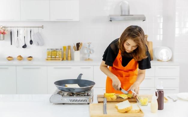 Mutter auf orangefarbener schürze, die neben fliegender pfanne und gasherd in der modernen heimküche steht und lernt, leckeres familienessen für kinder zu kochen, indem sie flohbrot halbiert.