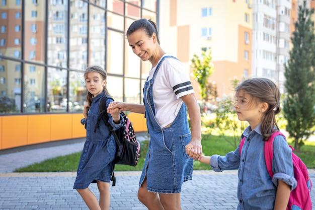 Mutter begleitet schüler zur schule, kinder mit schulranzen gehen zur schule.