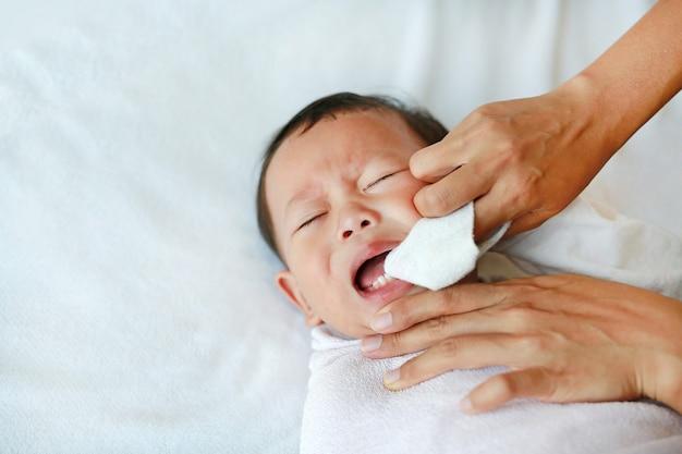 Mutter benutzen finger, um zunge und babys zähne mit sauberer gaze zu reinigen.