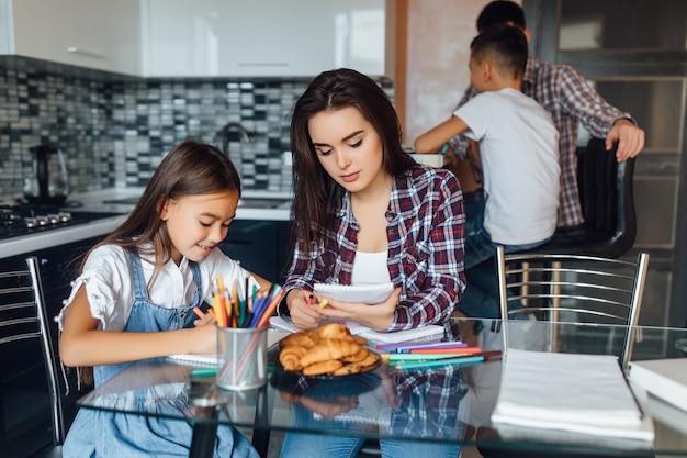 Mutter beobachtet etwas auf laptop, während zu hause küche zusammengehörigkeit sitzen