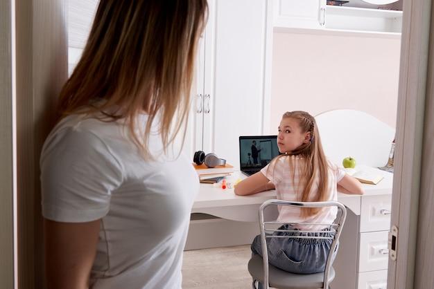 Mutter beobachtet ihre tochter, die hausaufgaben auf laptop zu hause macht raum betritt