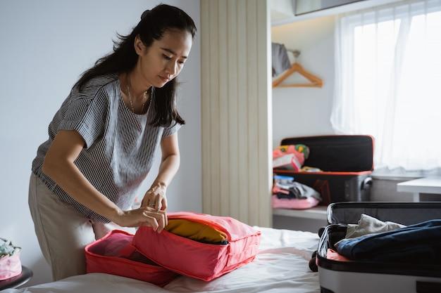 Mutter bereitet kleidung und taschen vor