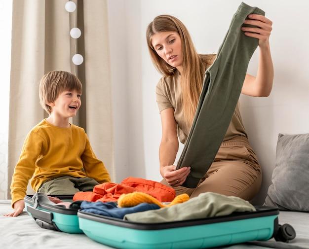 Mutter bereitet reisegepäck mit sohn vor