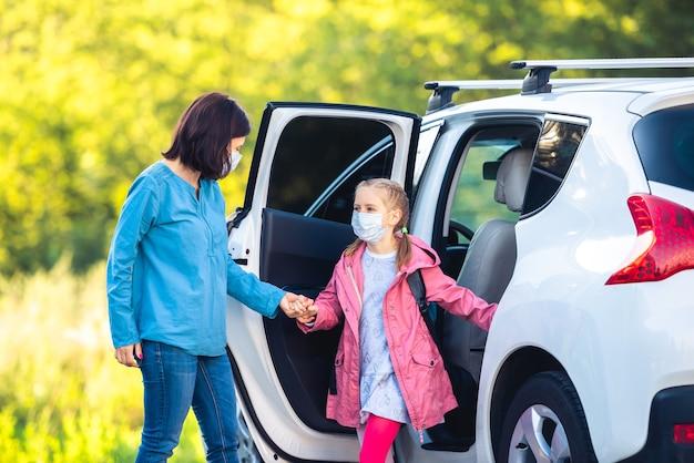 Mutter brachte tochter in schutzmasken im auto zurück zur schule