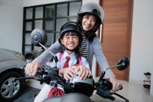 Mutter bringt ihre tochter morgens mit dem motorrad zur schule. asiatischer grundschüler in uniform, der zurück zur schule geht