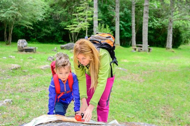 Mutter bringt ihrem sohn bei, kompass und karte in einem wald zu benutzen