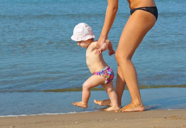 Mutter bringt ihrer tochter bei, zum strand zu gehen.