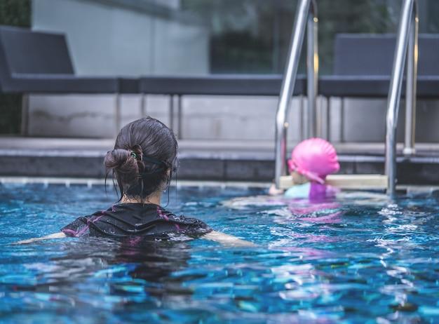 Mutter bringt ihrer tochter das schwimmen bei