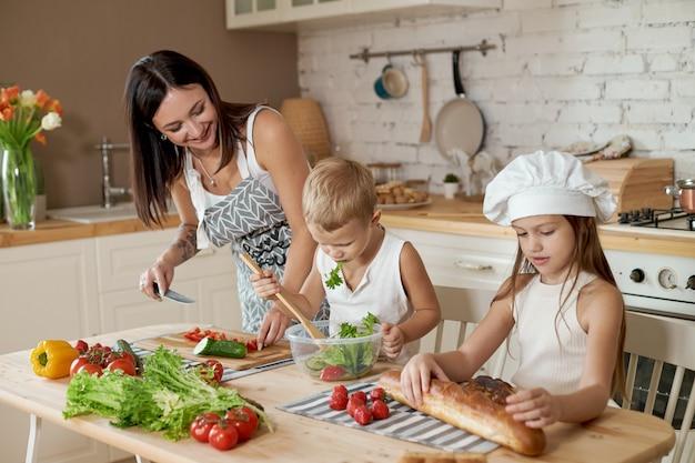 Mutter bringt ihrer tochter und ihrem sohn bei, einen salat mit frischem gemüse zuzubereiten