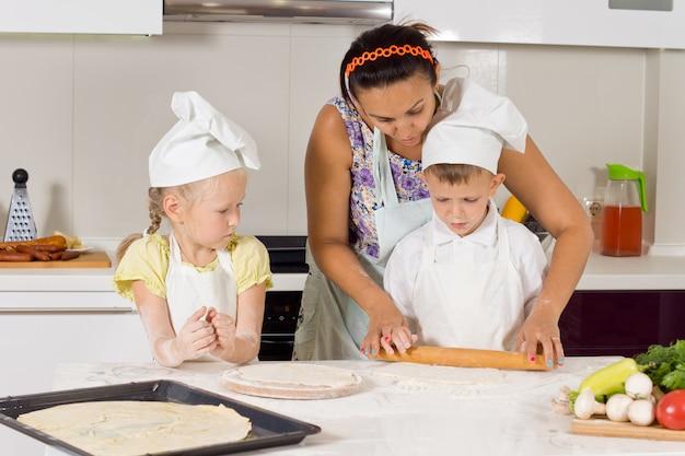 Mutter bringt kindern in kochkleidung in der küche bei, wie man pizza macht