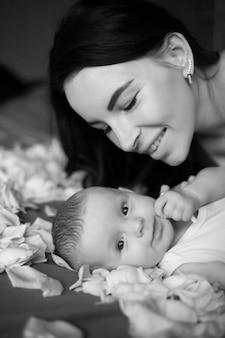 Mutter brünette mit einem neugeborenen jungen liegt mit weißen rosenblättern auf dem bett