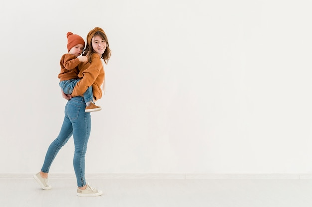 Mutter des hohen winkels, die piggyback fahrt ihrem sohn anbietet