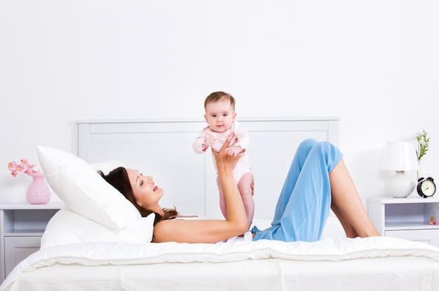 Mutter, die auf dem bett liegt und mit baby spielt