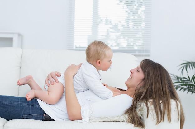 Mutter, die auf einem sofa hält ein baby auf ihrem kasten liegt
