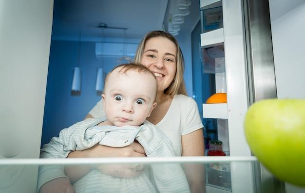 Mutter, die baby hält und grünen apfel vom apfel nimmt. blick von der innenseite des kühlschranks