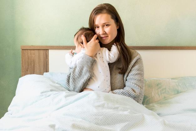 Mutter, die baby im bett umarmt