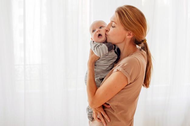 Mutter, die baby küsst und umarmt