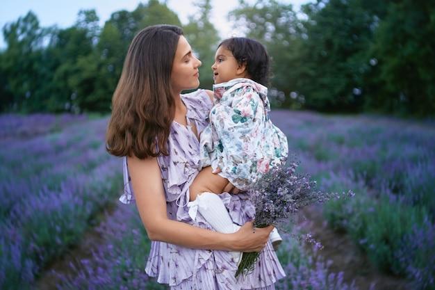 Mutter, die baby- und lavendelstrauß auf lavendelfeld trägt