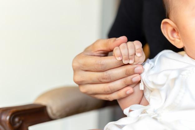 Mutter, die babyhand, liebe und familien-konzept hält.