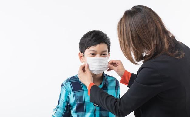 Mutter, die chirurgische maske für sohn trägt.