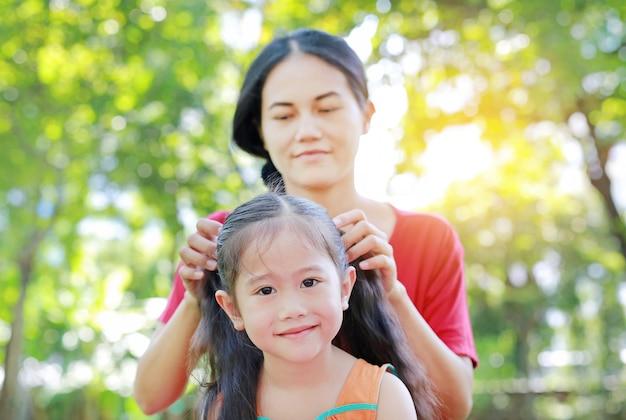 Mutter, die das haar der tochter kämmt, das im grünen garten liegt.