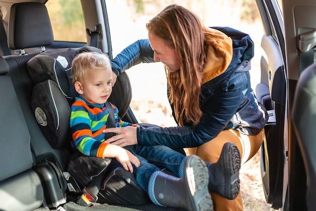 Mutter, die den sicherheitsgurt für ihren jungen in seinem autositz anlegt. sicherheit des kinderautositzes
