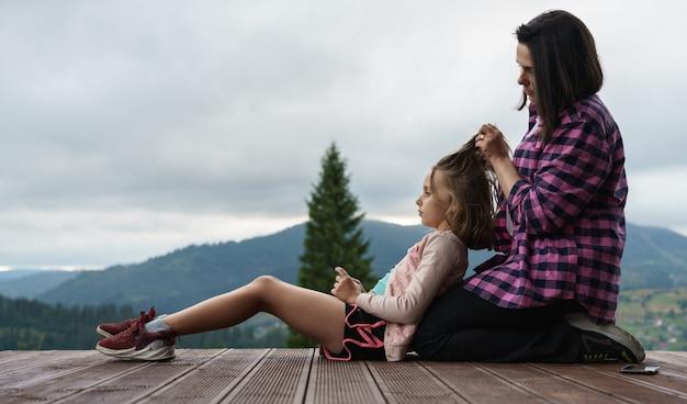 Mutter, die die haare der tochter im freien flechtet, während sie auf der terrasse mit kopierraum sitzt