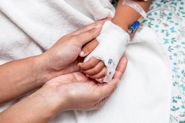 Mutter, die die hand des kindes hält, die iv-lösung im krankenhaus haben