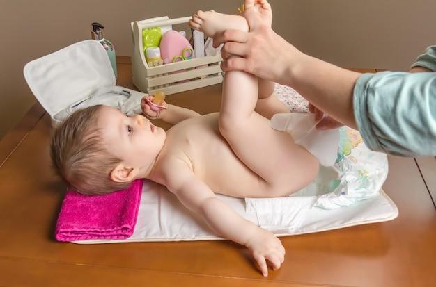 Mutter, die die windel eines entzückenden babys mit einem hygieneset für babys im hintergrund wechselt