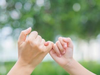 Mutter, die draußen eine Hand ihres Tages des Kindes im Frühjahr hält. Familienkonzept.