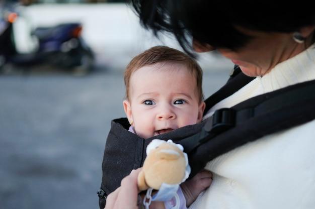 Mutter, die draußen ihr baby in einer babytrage trägt