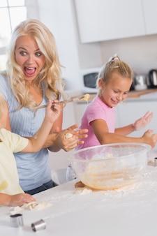Mutter, die ein gesicht macht, während ihre kinder sich um den teig kümmern