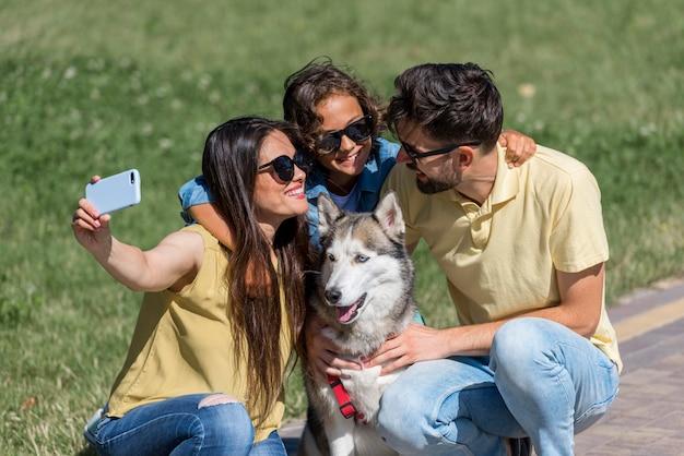 Mutter, die ein selfie der familie mit hund am park nimmt
