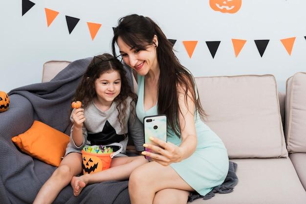 Mutter, die ein selfie mit tochter an halloween nimmt