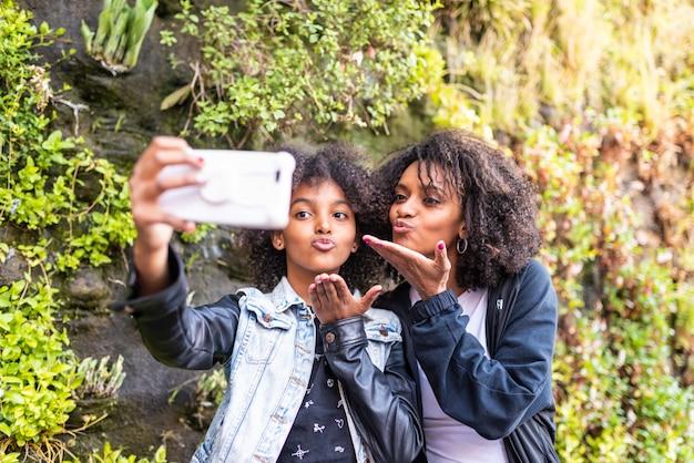 Mutter, die ein selfie mit tochter nimmt.