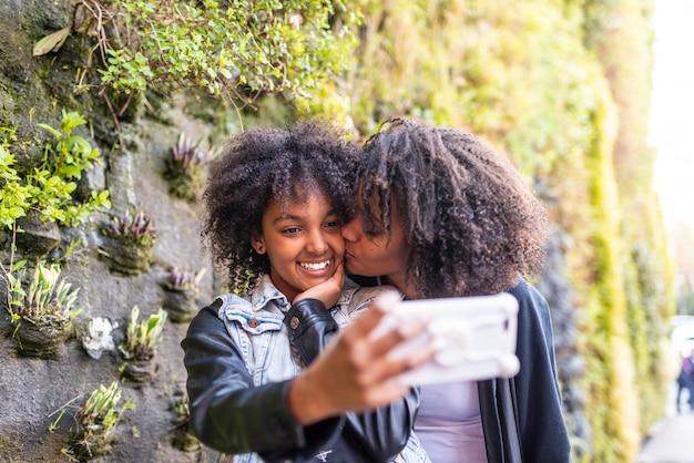 Mutter, die ein selfie mit tochter nimmt