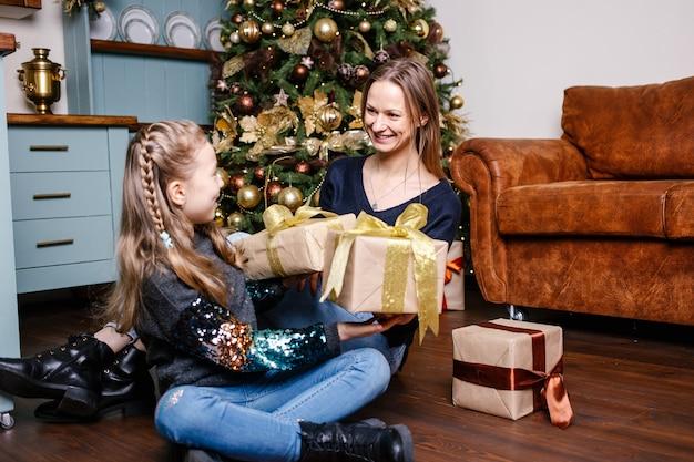 Mutter, die für tochter überraschen wird, gibt geschenk, nahe weihnachtsbaum zu hause. glückliches lächelndes mädchen erhält geschenk von mutter.