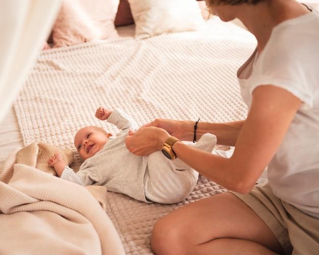 Mutter, die glückliches baby im bett kleidet