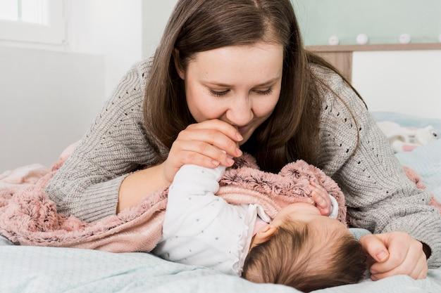 Mutter, die hand des schlafenden schätzchens küsst