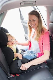 Mutter, die ihr baby im autositz sichert