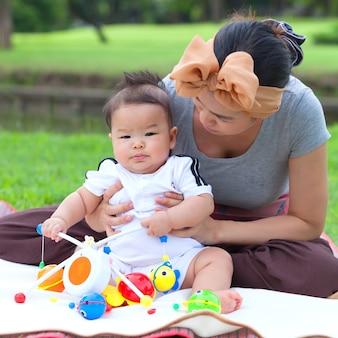 Mutter, die ihr kind im park trägt.