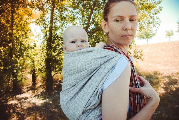 Mutter, die ihr kleines kind in einem tragetuch trägt