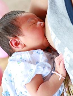 Mutter, die ihr neugeborenes kind stillt.