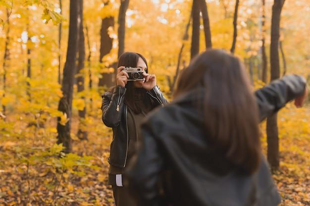 Mutter, die ihre charismatische tochter auf der retro-kamera im herbstpark fotografiert. hobbys und freizeitkonzept.