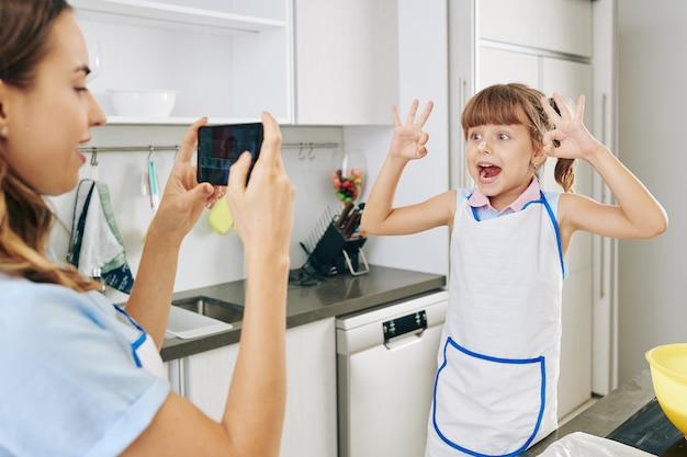 Mutter, die ihre tochter in der schürze fotografiert, die lustiges gesicht macht, wenn sie in der küche steht